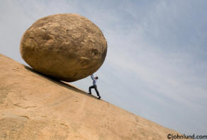 Picture of man pushing a boulder up hill