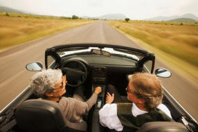 Picture of couple driving fast in convertable