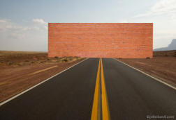 Picture of a brick wall accross a long straight road