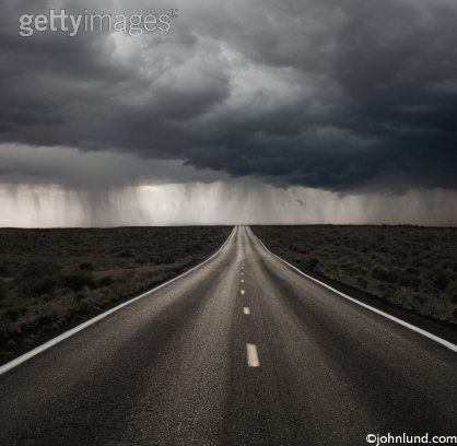 black & white photo of a road leading off into the distance with a storm in the background