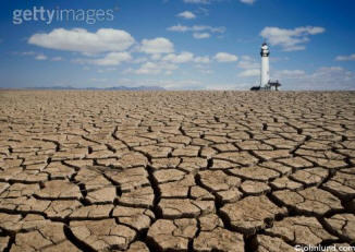 stock photo of a light house in a dry cracked mud setting