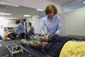 Medicine - woman physical therapist helps an African American patient