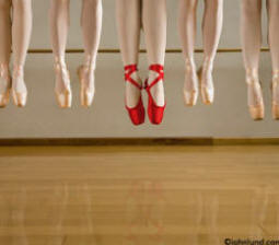 Shot of dancing shoes on dancers feet jumping into the air in unison with one pair of shoes bright red, the rest are gold dancing shoes
