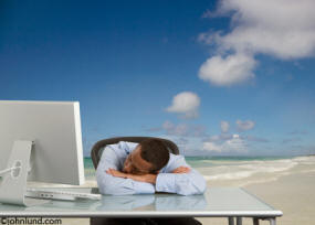 BlendImages - This picture is of an ethnic business man asleep at his desk dreaming of being on a beautiful ocean beach.