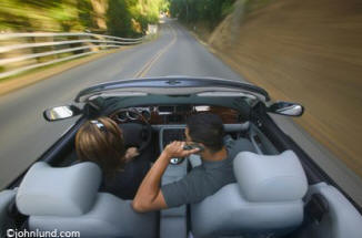 Lifestyle stock photo of a woman driving a convertable speedily along a long straight road with a man in the passenger seat on a cell phone.