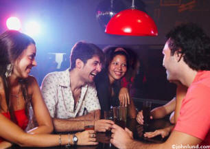 Lifestyle stock people photo of friends having drinks in disco bar, some are ethnic and all are happy