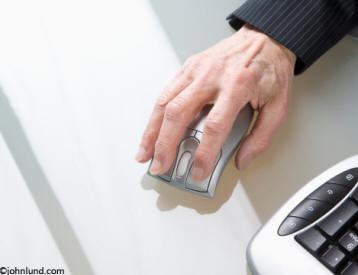 business stock photo of a senior womans hand on a computer mouse.