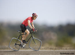 A cyclist strains as he attempts to ride a bicycle with square tires in a business, concept and lifestyle stock photo
