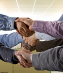 Picture of a 4 way handshake -  this handshake picture shows four sets of buisnessman's hands clasped in handshakes all at once in an office setting