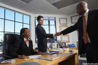Picture of a business meeting handshake. In this handshake photo two businessmen are shaking hands and a businesswoman is seated at a desk watching.
