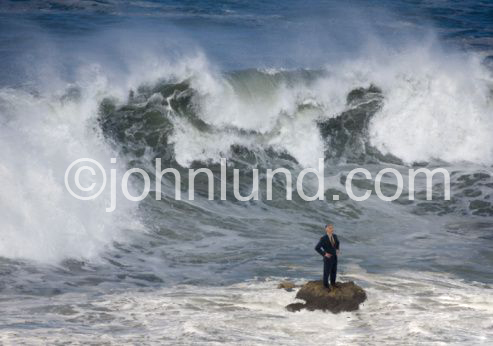 A huge wave sweeps up behind an unsuspecting businessman standing on a rock in the water.