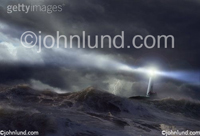 Beautiful unusual lighthouse pictures - A light house casts a beam over a rough sea in a stock picture about risk, danger, guidance and salvation.