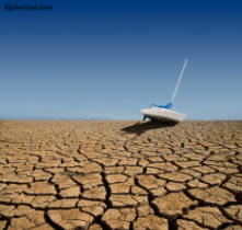 Stock Photo of Sail boat on dry cracked earth