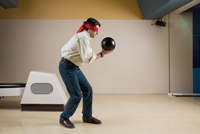 Picture of a man bowling with a blindfold on representing challange