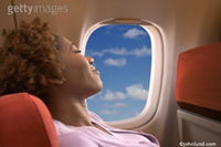 stock photo of ethnic woman on airplane or jet going on vacation getting away from it all