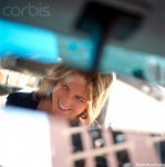 stock photo of a happy woman's face being reflected in the rearview mirror of a car