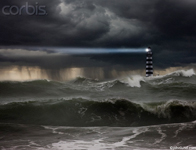 Picture of a light house with beam in a violent ocean storm