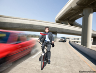 Bizzare stock photo of a man riding a bicycle on the freeway