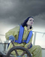 photo of woman at helm of boat in a storm
