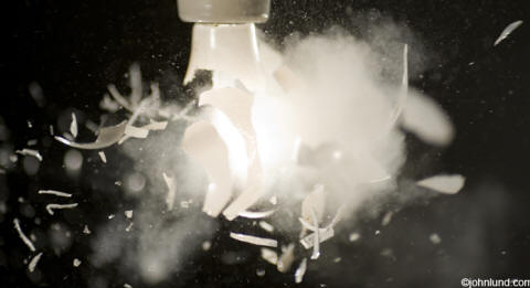 Stock photo of a light bulb at the moment it explodes in a cloud of dust a debris