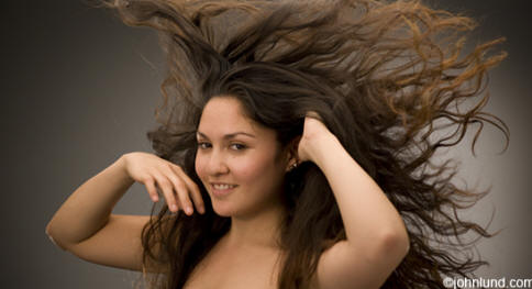 A still picture captures a moment when a Latina woman's hair is swirling around her smiling face