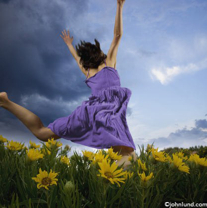 A woman wearing a flowing purple dress, runs free through a field of yellow daisies expressing her wild and natural side