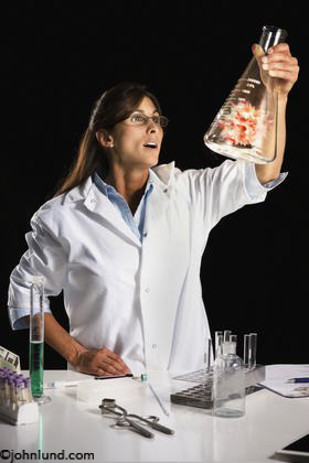 Picture of Energy Research and Development. A woman scientist holds up a beaker with a controlled explosion (cold fusion?) inside indicating experimental renewable energy sources. Energy research pics.
