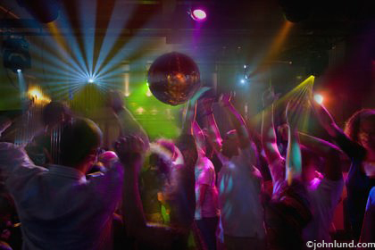 Pictures of a crowd dancing in a disco nightclub in Argentina. Wild crazy lighting, reds, purples, blues, strobe lights, and mirror balls.