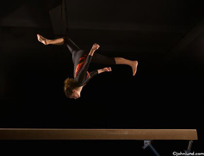 Picture of a young gymnast on the balance beam doing a flip, a metaphor for the skill, daring and flexibility needed to succeed in business and sports. The woman is inverted over the beam, head towards the ground and feet in the air.