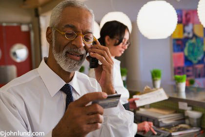 A black businessman calling in a credit card for a purchase colourmoves