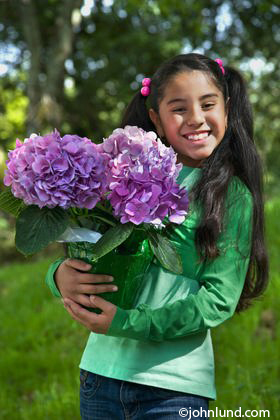 Smiling Young Hispanic Girl with Purple Flowers
