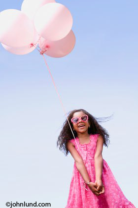 Photo Of A Young Black Girl With Pink Balloons And Curly Hair