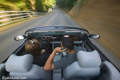 A convertible driven by a successful Hispanic woman down a scenic road with a male friend who is on his cell phone in a Jaguar XKR convertible.