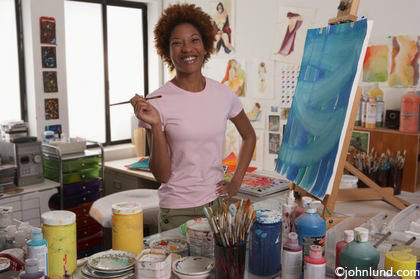 An African American artist smiles happily at the camera in the middle of her art studio and pausing from painting. She has a paint brush in one hand and the other hand is on her hip. She is wearing a pink blouse.