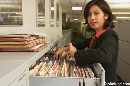 An Hispanic business woman searches through a filing cabinet, turns and looks into the camera.