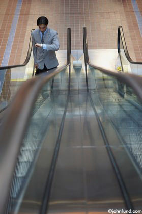 A businessman stands at the bottom of an up escalator and looks at his watch. The man is wearing a gray suit, and he is the only one on the escalators.