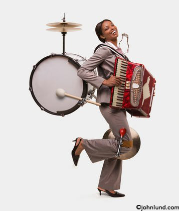 A woman wears numerous musical instruments as a one woman band concept stock photo. Picture of a one-woman band.  Photos of a woman playing musical instruments including a drum on her back and an accordion.