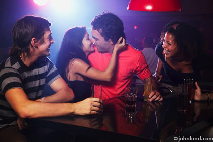 Picture of a couple kissing in a disco with friends looking on. Colored lighting with a redish glow. Two young women and two young men clubbing.