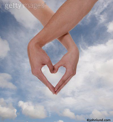 Two hands form a heart in this stock photo about love, friendship, togetherness and affection. The hands are against a summer sky.
