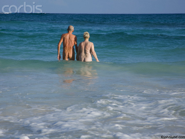 Pictures of a senior couple wading nude in the sea. The couple is a few yards out from the beach with the water about waist high. Picture taken from the couple's rear.
