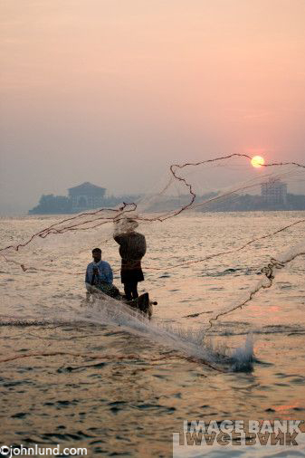 Fishermen throwing nets off the coast of Cochin, India at sunset with the sun hanging low in the sky. A scenic image from India.