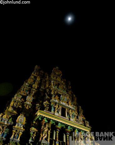 Photo of a Hindu temple in Madurai, India at night with the moon high above the temple spires.