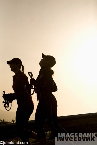 Silhouettes of two early morning runners holding exercise bands as they jog with the sun rising behind them. Both women are wearing baseball caps.