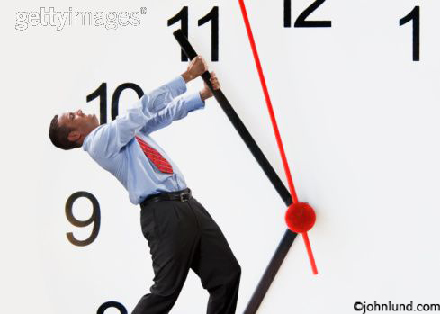 A business man is holding back the hands of time on a giant clock face. The businessman, an African American, is wearing a dress shirt, red neck tie and slacks. The man has a two handed grip on the minute hand.