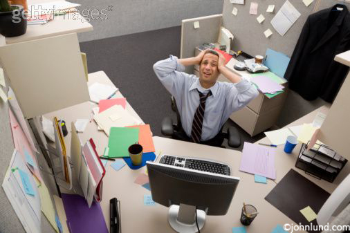 A frusrated business man in a cluttered cubicle feeling overwhelmed, stressed out, and under pressure.