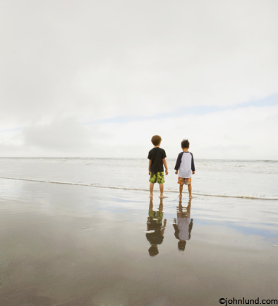 Pictures of two young boys at an ocean beach. They stand together and look out to sea as thier reflections glimmer in the wet sand.