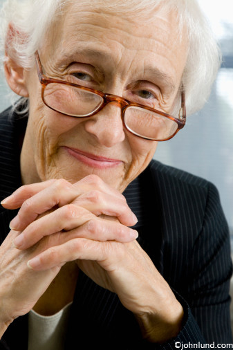 Senior business woman wearing glasses, hands folded in front of her, looking benevolent and pleased. Older woman peering over the top of her glasses.