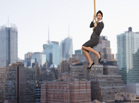 Pictures of a woman hanging at the end of her rope with New York City in the background.