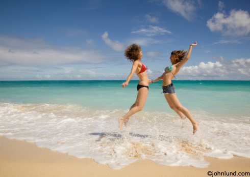 Picture of a mother and daughter enjoying time together on a secluded beach. Quality time with family while on vacation in Hawaii. Beautiful scenic beach with green water and blue skies.