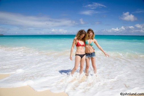 Photos of a mother and her daughter enjoying time together on a secluded beach in Hawaii.  The two women have their feet in the waves breaking on the beach. White water around their bare feet.
